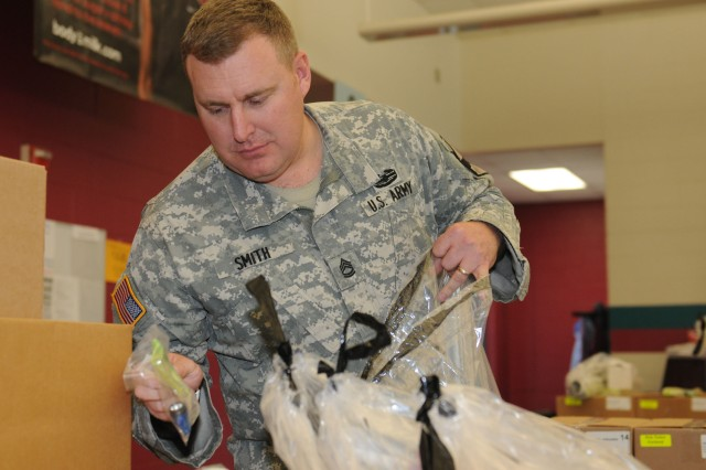 FORT HOOD, Texas-- Sgt. 1st Class Cory Smith, the fire support noncommissioned officer assigned for 1st Squadron, 9th Cavalry Regiment, 4th Brigade Combat Team, 1st Cavalry Division, organizes fundraiser orders, Nov. 3, 2011, at Brookhaven Elementary School. Soldiers assisted the unit's adopted school with the fundraiser to strengthen their partnership with the school and local community.