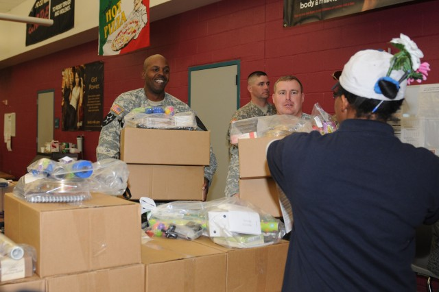 FORT HOOD, Texas--Sgt. Leonard Little (left) and Sgt. 1st Class Cory Smith (right), both assigned to Headquarters and Headquarters Troop, 1st Squadron, 9th Cavalry Regiment, 4th Brigade Combat Team, 1st Cavalry Division, bring ordered fundraiser items to a Brookhaven Elementary School parent , Nov. 3, 2011. Soldiers carried packages to the vehicles of Brookhaven Elementary School parents to help their adopted school.