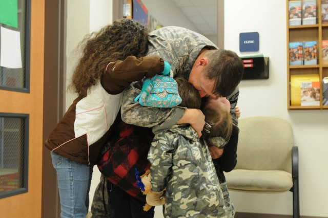 FORT HOOD, Texas-- Sgt. Quentin Johnson hugs four of his children after arriving back to Fort Hood Dec. 15 following a deployment with 2nd Brigade Combat Team, 1st Cavalry Division.