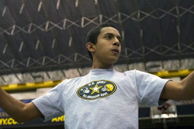 Michael Thompson, an Army Junior ROTC Cadet from Miami Sunset Senior High School, Fla., directs the All-American Bowl Marching Band during a practice Tuesday in the Alamodome in San Antonio.