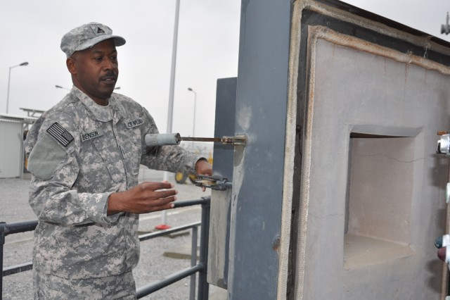 Construction Representative Keith Benson, who supports Corps of Engineers construction from the Afghanistan Engineer District-North's Bagram Area Office, opens a hyeavy door to one of the van-sized burn chambers at the new trash disposal plant at Bagram Airfield recently.  When in use, the chambers reach 1,800 degrees Fahrenheit.
