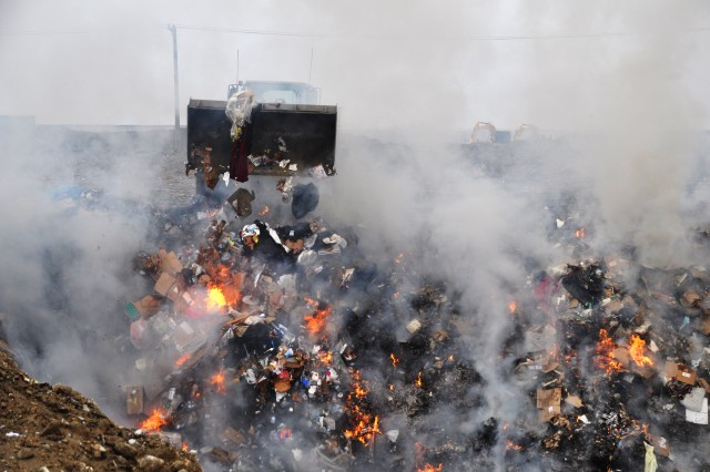 A bulldozer dumps a load of trash into a burn pit just 300 yards from the runway at Bagram Airfield.  A recently completed $5.5 million trash disposal plant reduces the amount of smoke and air pollution generated when the unwanted debris was burned in an open pit or in several small incinerators.