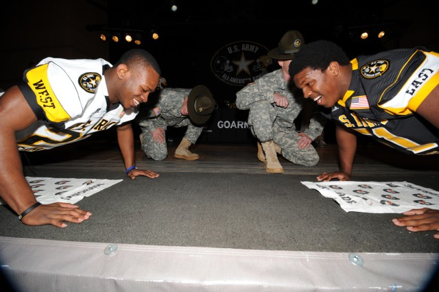 West defensive back LaDarrell McNeil (left) of Wilmer-Hutchins High in Dallas goes head-to-head against East linebacker Keith Brown of Norland Senior High in Miami as part of the push-ups competition Wednesday night during the Player-Hero Challenge at Sunset Station in San Antonio. The event was part of the pre-game festivities for the 2012 U.S. Army All-American Bowl set for Saturday.