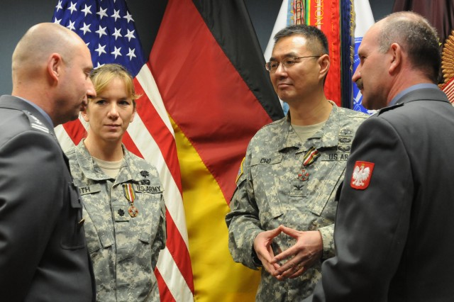 The (From left) Col. Stefan Walowski, the Polish senior national representative for Ramstein, Lt. Col. Rachele Smith, the Mannheim Army Health Center and Coleman Troop Medical Clinic commander, Col. John M. Cho, the 30th Medical Commander commander, and Lt. Col. Zenon Pilat, the polish team chief at Ramstein, speak together following the Polish Armed Forces Medal presentation Dec. 15, 2011. Cho and Smith were presented Polish Armed Forces Medals (Silver) on behalf of the Polish Minister of Defense, for their work while serving at Landstuhl Regional Medical Center and their support to wounded Polish service members receiving treatment there. (U.S. Army photo by Sgt. 1st Class Christopher Fincham)