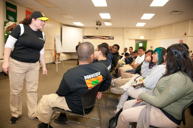 Erica Bertoli, left, outreach program manager, Communications-Electronics Research, Development and Engineering Center, engages students at San Antonio's Sam Houston High School Jan. 5, 2012, as part of outreach efforts during U.S. Army All-American Bowl Week.