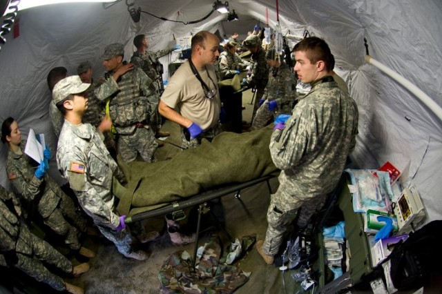 Soldiers from the 67th Forward Surgical Team (Airborne) discuss medical treatment on a simulated wounded soldier during a medical exercise, Miesau, Germany, Feb. 16, 2011. The 67th Forward Surgical Team is the only airborne forward surgical team in Europe and one of only five units Army-wide. (U.S. Air Force photo/TSgt Wayne Clark, AFNE Regional News Bureau) (Released)