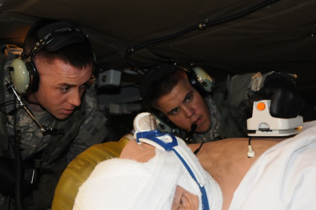 """Spc. Brandon Mosher and Spc. Cody Ford, 1st Battalion, 223rd Aviation Regiment Air Ambulance Detachment, """"Flatiron"""" unit, go through a training exercise in the current Medevac simulators Dec. 14. Officials say, research and demonstrations on future Medevac helicopters will allow for more space, faster speed and reduced risk of fatality in theater."""