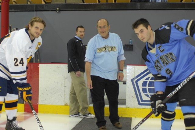 Chris Perry, a prostate cancer survivor and Office of the Directorate of Intercollegiate Athletics IT specialist (center), dropped the ceremonial puck for Army captain senior Michael Hull (right) and Canisius captain senior Scott Moser (left) before the opening faceoff at the Jan. 6 Army-Canisius hockey game. The Army team wore blue jerseys to promote prostate cancer awareness as part of the event which also included T-shirts for the first 1,000 fans. Photo by Paul Rader/NETCOM