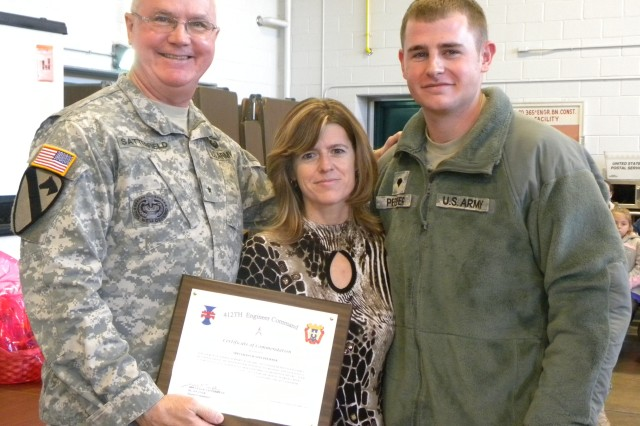Spc. Justin Pfeiffer, a medic with the 365th Engineer Battalion, was recently recognized by his leadership for spearheading a successful fundraising event to support the unit's Family Readiness Group.  Pfeiffer is pictured with his mother, Jodie Miller, and Brig. Gen. Douglas R. Satterfield, deputy commanding general of the 412th Theater Engineer Command, following the awards ceremony in Schuylkill, Pa., Dec. 11, 2011. (Photo: 2nd Lt. Renee Zimmerman)