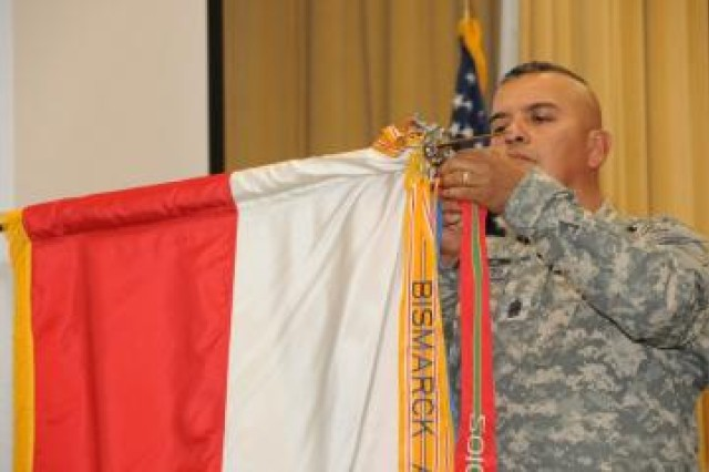 Command Sgt. Maj. Gabriel Cervantes, Army South command sergeant major, attaches the Army Superior Unit Award streamer on the U.S. Army South unit colors Oct. 4, 2011, during a ceremony on Fort Sam Houston, Texas.