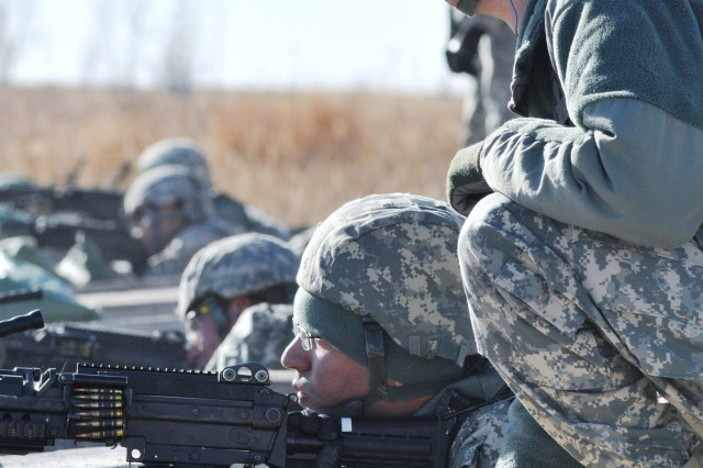 Sgt. William Bungard, right, coaches Spc. Elmer Ortiz during a range for Division Headquarters and Headquarters Battalion, 1st Infantry Division Soldiers at Fort Riley, Kan., Jan. 9. Both Soldiers are assigned to Headquarters Support Company, DHHB.