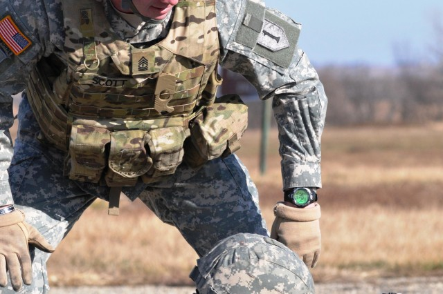 First Sgt. Larry Scott, senior noncommissioned officer of Headquarters Support Company, Division Headquarters and Headquarters Battalion, 1st Infantry Division, observes Spc. Jeremy Johnson, also assigned to HSC, DHHB, clearing his weapon at a Fort Riley, Kan., firing range Jan. 9.