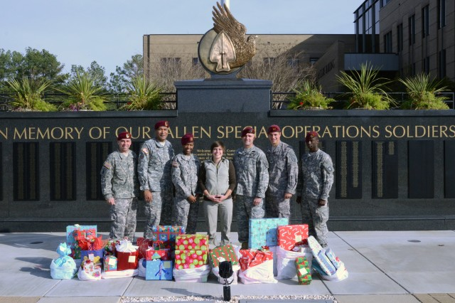 Chaplains and Chaplain Assistants from various units within the United States Army Special Operations Command stand with Brittney Grider (center) in front of the USASOC Memorial Wall in Meadows Memorial Plaza, Fort Bragg, N.C. on Dec 20. Grider is the widow of Aaron Grider, and part of the Aaron Grider Foundation, which donated presents for families within USASOC.