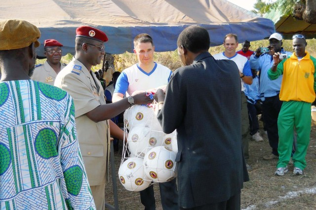 The commander of the 2nd Military Region in Burkina Faso presents a gift of soccer balls to the mayor of Samagan as part of a community service project that brings together villages and the troops assigned to protect them, Nov. 26, 2011.