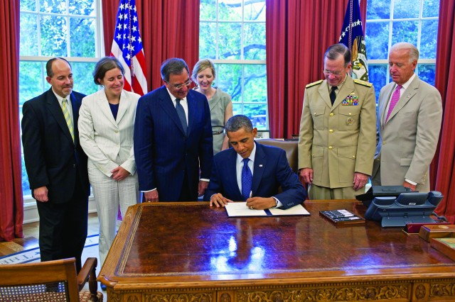 """As Secretary of Defense Leon Panetta; Kathryn Ruemmler, counsel to the president; and then-Chairman of the Joint Chiefs of Staff Adm. Mike Mullen look on, President Barack Obama signs the certification stating the statutory requirements for repeal of """"don't ask, don't tell"""" have been met July 22, 2011, in the Oval Office."""