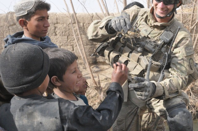 Sgt. Adam Lundy, a team leader for 2nd Platoon, B Company, 1st Battalion, 5th Infantry Regiment, 1st Stryker Brigade Combat Team, 25th Infantry Division, and some children play with a crab pulled from the stream while on patrol in the village of Shengazi, Afghanistan, Jan. 3, 2012.