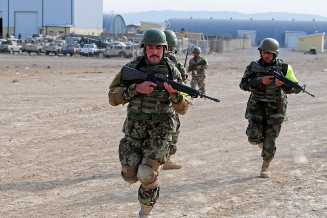 Afghan National Army soldiers from the 2nd Brigade, 205th Corps Noncommissioned Officer Academy, distinguished by their green armbands, move swiftly as a squad element toward a village during a training scenario on Forward Operating Base Eagle in Zabul province Jan. 10. Command Sgt. Maj. Kafayatullah, 205th Corps command sergeant major, along with other Afghan, U.S. and Australian enlisted leaders visited the academy to see the progress being made by ANA soldiers during their four-week course. Students are distinguished by their bright green armbands, while the cadre wears bright blue. Visitors were able to observe demonstrations that included room-clearing procedures, searching shops, questioning locals, and reacting to and successfully handling the discovery of an improvised explosive device. (Photo/U.S. Army Sgt. Amanda M. Hils)