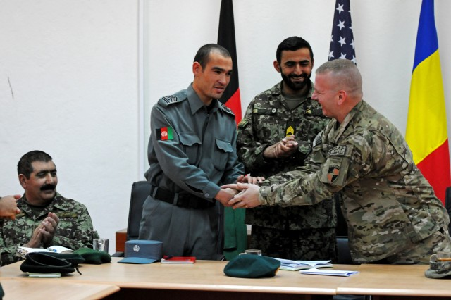 Command Sgt. Maj. John W. Troxell thanks Afghan National Police Command Sgt. Maj. Abdul Zafar, ANP command sergeant major, as Afghan National Army Command Sgt. Maj. Kafayatullah, 205th Corps command sergeant major, and ANA Col. Mohammed Wazir Akbari, 2nd Brigade, 205th Corps commander, look on during a meeting on Forward Operating Base Eagle in Zabul province Jan. 10. Kafaytullah, Zafar and Troxell, along with other Afghan, U.S. and Australian enlisted leaders visited the 2nd Brigade, 205th Corps Noncommissioned Officer Academy to see the progress being made by ANA soldiers during their four-week course. Students are distinguished by their bright green armbands, while the cadre wears bright blue. Visitors were able to observe demonstrations that included room-clearing procedures, searching shops, questioning locals, and reacting to and successfully handling the discovery of an improvised explosive device. (Photo/U.S. Army Sgt. Amanda M. Hils)
