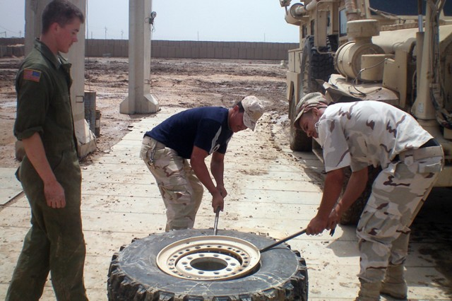 A Soldier with Trp. C, 1-3 Cav. Regt., supervises Iraqi mechanics repairing a tire on Patrol Base Hussayniyah in June 2010. Iraqi and U.S. Soldiers worked together to train on proper vehicle maintenance procedures. (U.S. Army photo by Spc. Adam Hefner, 3rd Cav. Regt. Public Affairs)