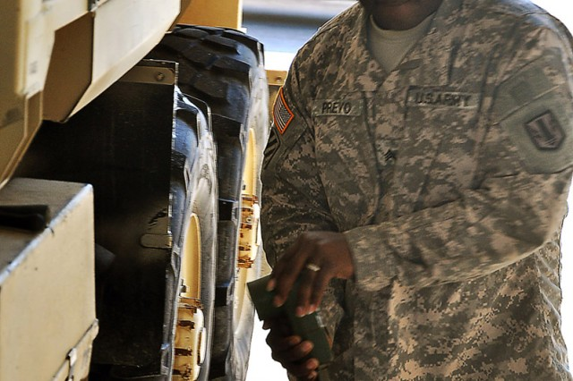 Sergeant Renardo Prevo, a track mechanic with the combat repair team for Btry. B, 2-20 FA Regt., 41st Fires Bde., pulls out a set of cables while performing maintenance on an M-270 Multiple Launch Rocket System in the unit's motor pool Jan. 6. (U.S. Army photo by Staff Sgt. Kyle Richardson, 41st Fires Bde. Public Affairs)