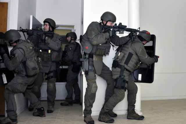 FBI SWAT team members enter a room and break out into right and left formations at Watervliet Arsenal, N.Y.  At all times they had 360 degree situational awareness.