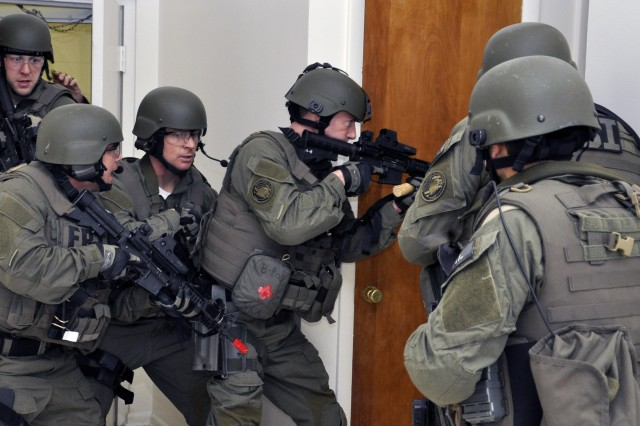 FBI SWAT team members enter a room and start to clear a hallway that led to several bedrooms at Watervliet Arsenal, N.Y.