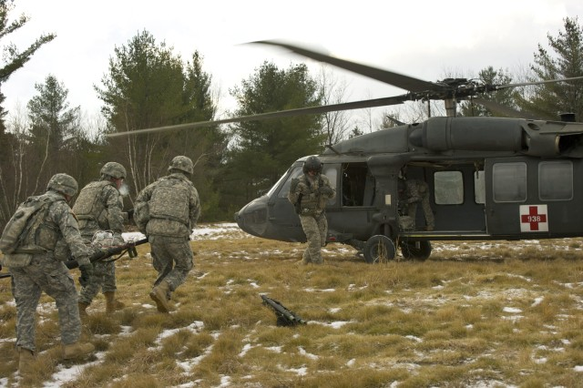Medics from 3rd Battalion, 6th Field Artillery Regiment, 1st Briagde Combat Team, carry a simulated casualty to a UH-60 Black Hawk helicopter Jan. 9 as part of Fort Drum's initial medevac training exercise.