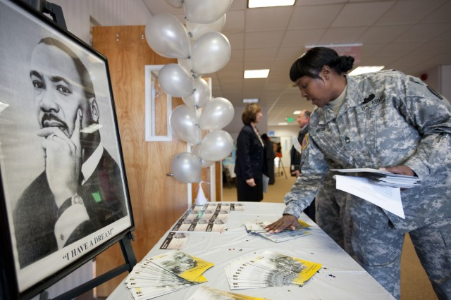 Sgt. 1st Class Natasha Bass of the installation's Equal Opportunity Office places pamphlets and programs for the Dr. Martin Luther King Jr. Day community observance on a table near the entrance of McGill Training Center on Jan 12. Several hundred service members and civilians attended