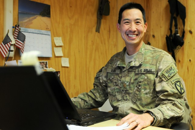 Maj. Charles Djou sits at his desk in the Task Force Spartan legal office in Southern Afghanistan.