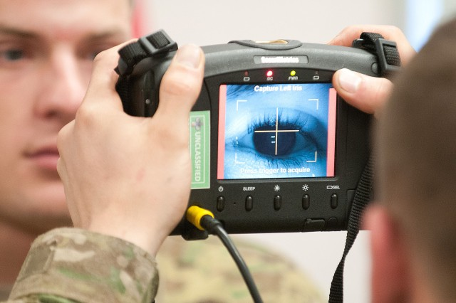 A paratrooper scans the iris of another using a Handheld Interagency Identity Detection Equipment, or HIIDE, system during training, Jan. 10, 2012, at the Joint Readiness Training Center, Fort Polk, La.  The device measures personal biometric data that allow friendly forces to identify persons of interest at a later date.