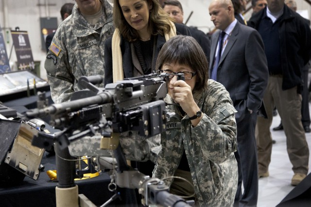 Heidi Shyu, the acting assistant secretary of the Army for Acquisition, Logistics, and Technology, looks through the sights of the M240H, a 7.62mm medium machine gun mounted to helicopters.