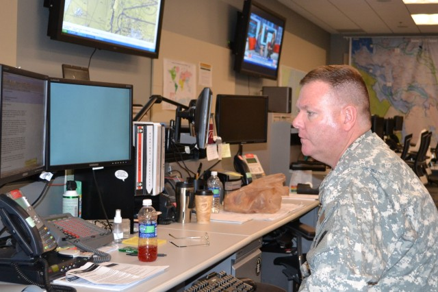 U.S. Army Lt. Col. Gerald Pembroke, the battle captain assigned to SDDC's Command Operations Center, reviews incoming messages.  Personnel assigned to COC are responsible for planning, directing, synchronizing, coordinating and monitoring global surface movements and port operations through subordinate operational commands and strategic seaports.  The COC maintains operational oversight of all SDDC operations. (U.S. Army photo by Mark Diamond, Hq. SDDC Public Affairs)
