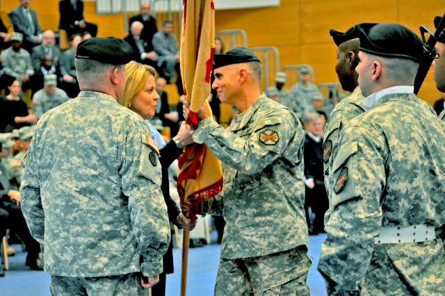 Col. David H. Carstens accepts the U.S. Army Garrison Wiesbaden colors from Kathleen Marin, Installation Management Command Europe Region director, as outgoing garrison commander, Col. Jeffrey Dill (left), looks on.