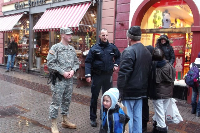 Pfc. Jacob Dummitt, 529th Military Police Company, left, and Polizeihauptmeister Sven Stadtrecher, German police liaison, greet residents during their joint patrol at the Heidelberg Christmas market in December. The patrols are designed to foster greater understanding between German and American police forces and increase overall security, safety and cooperation for members of the public.