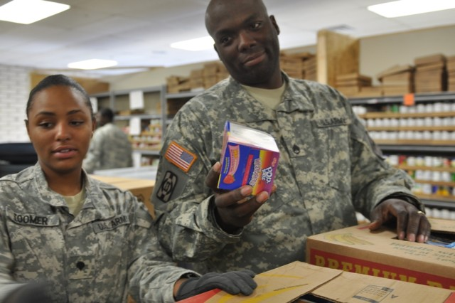 Staff Sgt. Frederick Burke, a petroleum supply NCO, passes a box of non-perishable breakfast food to Spc. Charika Toomer, a motor transport operator, so that they can be placed into a basket for delivery to needy families. The Soldiers, both in HHC, 47th BSB, 2nd BCT, 1st AD, volunteered to help with the packing and organizing of the food at the Kelly Memorial Food Pantry, Dec. 13.