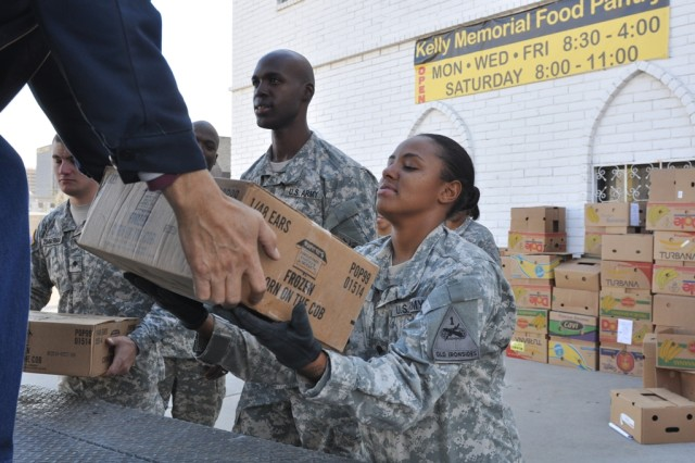 Specialist Crystal Edmond, a chaplain's assistant in 47th BSB, 2nd BCT, 1st AD, helps unload frozen corn on the cob from food delivery truck at the Kelly Memorial Food Pantry, Dec. 13. The Kelly Memorial Food Pantry provides food, free of charge, twice a month to those who qualify on an income or emergency based need.