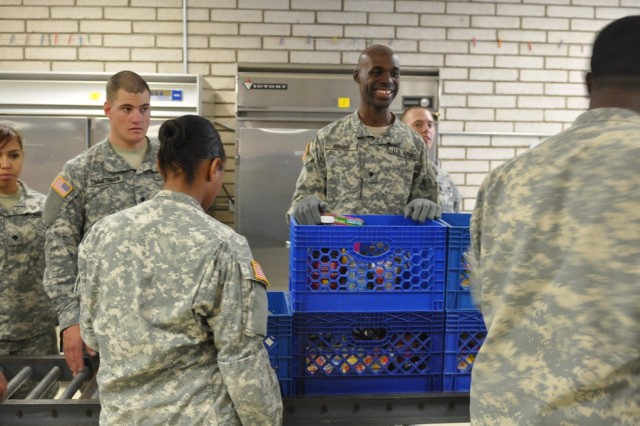 Specialist Jonathan Wright, a human resources clerk with HHC, 47th BSB, 2nd BCT, 1st AD, smiles as he helps pack baskets of food for families in need at the Kelly Memorial Food Pantry, Dec. 13. Soldiers from the 47th BSB have been volunteering at the pantry since March 2011.