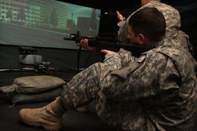 FORT CARSON, Colo. -- Sgt. Steven Glass, 7th Squadron, 10th Calvary Regiment, 1st Brigade Combat Team, 4th Infantry Division, fires a modified M4 carbine rifle in an Engagement Skills Trainer Jan. 9 at the Training Support Center. Inside the new 80,000-square-foot center, the entry area opens to a spacious hallway, which leads to a training coordinator room, a stadium-style call-for-fire training area and two Engagement Skills Trainers.