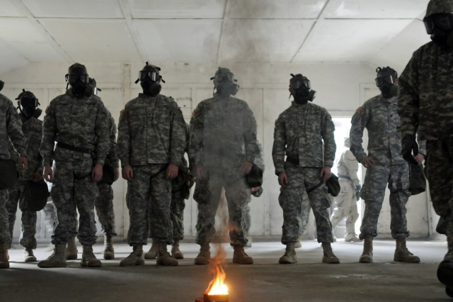 "Soldiers with B Troop, 6/8 Cav. Regt., 4IBCT, 3rd Inf. Div., stare at the smoke caused by burning CS gas capsules, Jan. 9, during quarterly Chemical, Biological, Radiological and Nuclear training on Fort Stewart, Ga. ""Bushmaster"" Soldiers received refresher training on the proper wear of the field protective mask and the Joint Service Lightweight Integrated Suit Technology protective garment, and gained confidence in their equipment by unmasking in the gas chamber."
