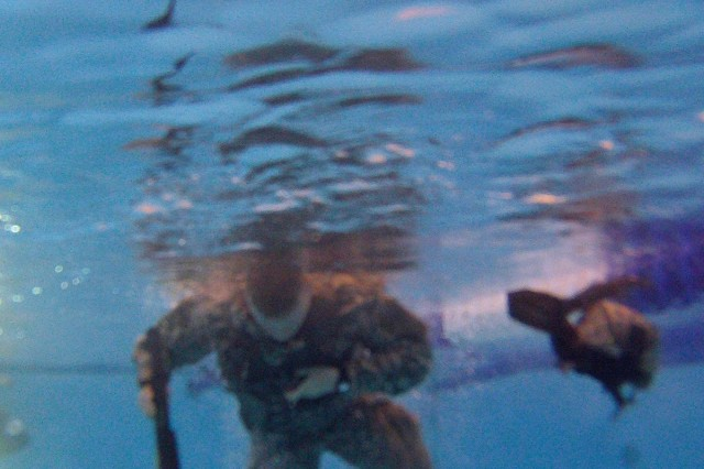 A Soldier with B Troop, 6/8 Cav. Regt., 4IBCT, 3rd Inf. Div., attempts to remove a load-bearing vest just under the surface of the water after plunging blindfolded into a pool, Jan. 5, during combat water survivability training at Fort Stewart.