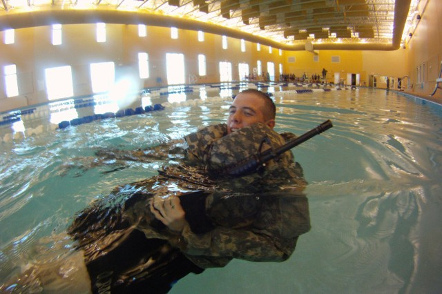 "Sergeant Bryan M. Beisell, a native of Eagle Grove, Iowa, and a cavalry scout with B Troop, 6th Squadron, 8th Cavalry Regiment, 4th Infantry Brigade Combat Team, Third Infantry Division, uses ACU trousers as a flotation device, Jan. 5, during combat water survivability training held at Fort Stewart. ""Bushmaster"" Soldiers began the training by being pushed, blindfolded, off diving boards while wearing Kevlars and load-bearing vests, and while carrying dummy rifles. See story and photos on page 3A."