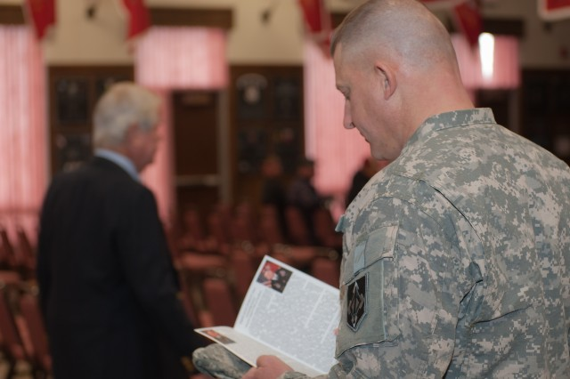 A U.S. Army Soldier reviews the program for Maj. Gen. Yenter's promotion ceremony held Jan. 18, 2012. Yenter was promoted to the rank of major general.