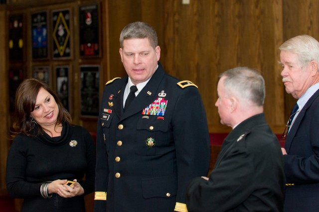 Maj. Gen. Mark Yenter, his wife, Lisa, Maj. Gen. Merdith Temple and retired Lt. Col., Ken Yenter, talk briefly before Yenter was officially promoted to the rank of major general. Yenter was nominated for the appointment in July 2011 for his qualities of patriotism, valor, fidelity, his abilities and his demonstrated potential for increased responsibility. He is authorized and directed to wear the uniform and two-star insignia of major general effective Jan. 18, 2012.