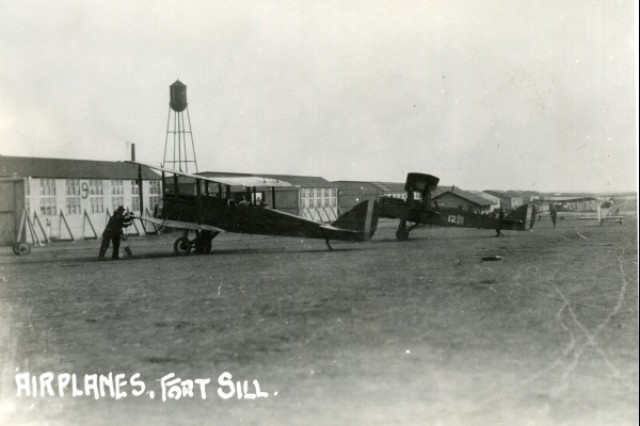 "A crewman works on a Curtis JN-4 ""Jenny"" airplane at Henry Post Army Airfield in 1916. Army combat aviation was born at Fort Sill when the 1st Aero Squadron was formed here in 1915 with eight ""Jennys."" The airfield was a sod runway with makshift wooden hangars; it was not paved until 1946."