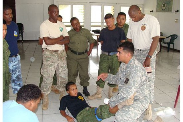 "LADYVILLE, Belize "" Sgt. 1st Class Erik Adams (kneeling), conducts a combat medic engagement with members of Belize's Defence Force and Navy while Sgt. 1st Class Don Berry (standing behind Adams) looks on Nov. 2011. (Photo courtesy of Sgt. 1st Class Efrem Dicochea, U.S. Army South Surgeon's Office operations noncommissioned officer)"
