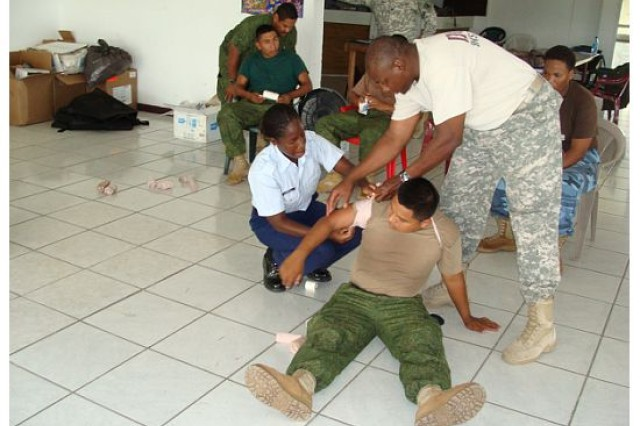 "LADYVILLE, Belize "" Sgt. 1st Class Don Berry (right), conducts a combat medic engagement with members of Belize's Defence Force and Navy Nov. 2011. (Photo courtesy of Sgt. 1st Class Efrem Dicochea, U.S. Army South Surgeon's Office operations noncommissioned officer)"