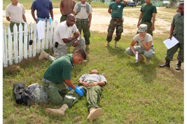 "LADYVILLE, Belize "" Sgt. 1st Class Don Berry (kneeling on the left), watches as members of Belize's Defence Force and Navy conduct a combat medic engagement while Spc. Kia Wilson (kneeling on right) looks on Nov. 2011. (Photo courtesy of Sgt. 1st Class Efrem Dicochea, U.S. Army South Surgeon's Office operations noncommissioned officer)"
