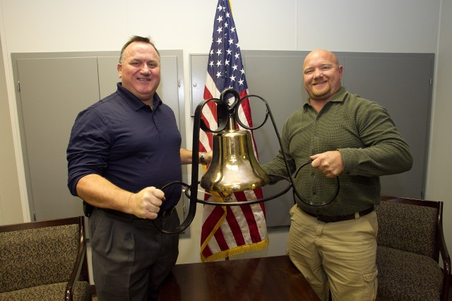 Anniston Army Depot Director of Production Jeff Simmons, left, and Deputy Director of Production Tommy Carlisle pose with the brass locomotive bell presented by the Defense Non-Tactical Generator and Rail Center, a component of the depot located in Utah.