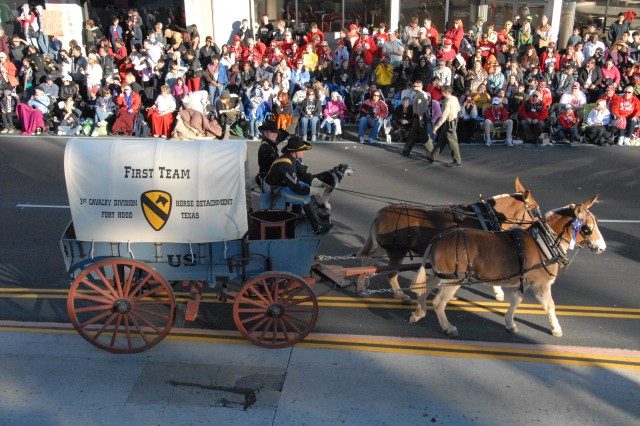 """PASADENA, Calif. --Spc. Will Smith,  a fire control repairer and currently the """"swamper,"""" or the assistant to the driver of the mule team, waves to the crowd as Sgt. Chistopher Kabela, a cavalry scout and the """"muleskinner"""", or driver of the mule team, both of the 1st Cavalry Division's Horse Cavalry Detachment, drives mules Tina & Dolly, with some help from the barking SGT Buddy, at the Tournament of Roses Parade Jan. 1 in Pasadena, Calif."""