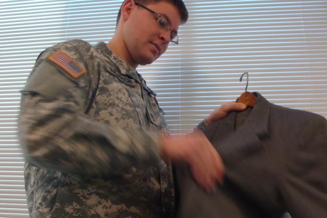 A Soldier prepares to don a civilian business suit.